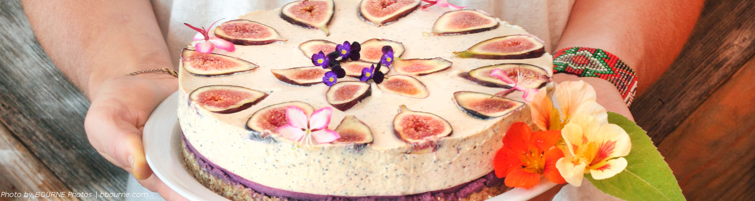 close up of a fig cake decorated with edible flowers being held by someone.
