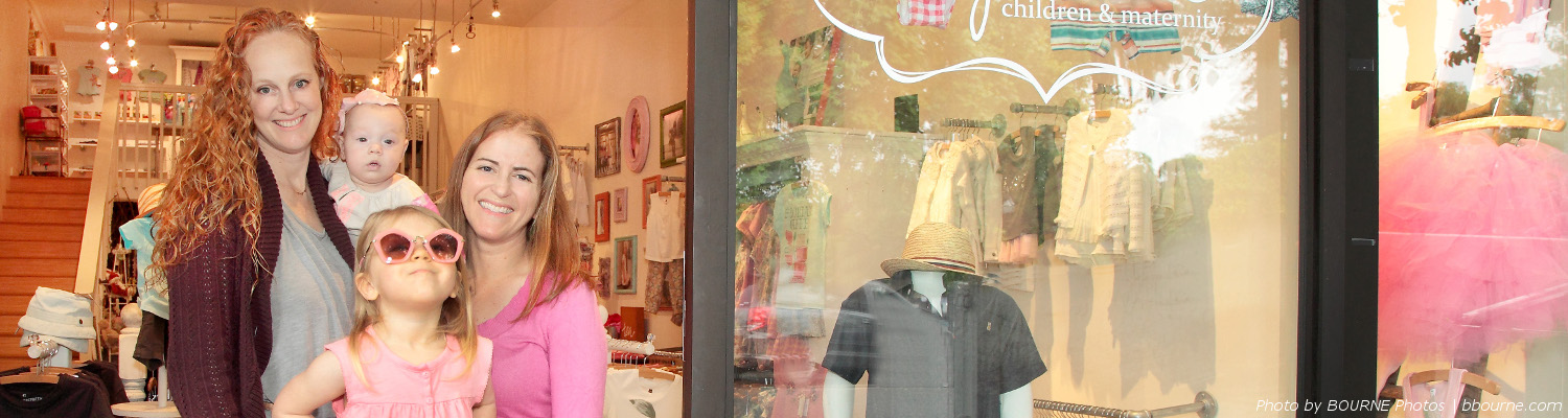 two adults, child, and baby standing in window of children's clothing store, cupcake, in downtown healdsburg.