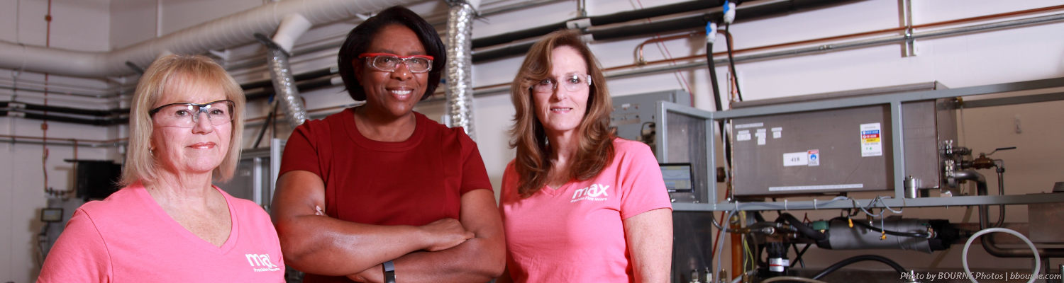 three woman side by side posing for picture at max machinery manufacturing facility.